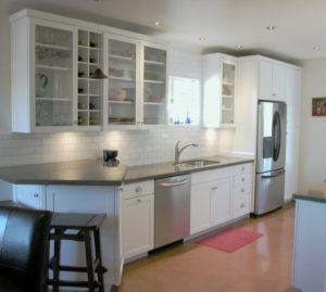 Grey concrete countertops with white brick feature